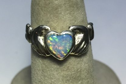 Firey heart shaped opal set in the hands of love, the claudaugh.